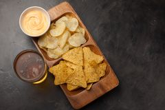 Beer in glasses closeup on the concrete table. Beer and snacks are chips and nachos in wooden bowl with cheese souce. top view. Co. Py space. Drink and snack for Royalty Free Stock Images