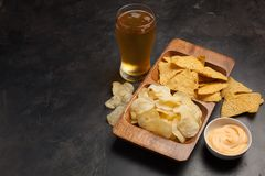 Beer in glasses closeup on the concrete table. Beer and snacks are chips and nachos in wooden bowl with cheese souce. top view. Co. Py space. Drink and snack for Stock Photography