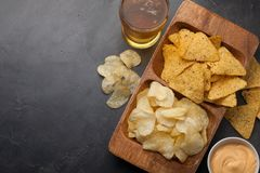 Beer in glasses closeup on the concrete table. Beer and snacks are chips and nachos in wooden bowl with cheese souce. top view. Co. Py space. Drink and snack for Royalty Free Stock Image