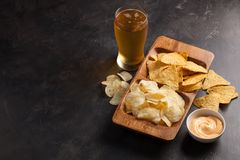 Beer in glasses closeup on the concrete table. Beer and snacks are chips and nachos in wooden bowl with cheese souce. top view. Co. Py space. Drink and snack for Stock Photos