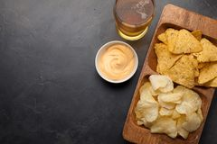 Beer in glasses closeup on the concrete table. Beer and snacks are chips and nachos in wooden bowl with cheese souce. top view. Co. Py space. Drink and snack for Stock Photo