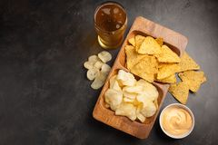 Beer in glasses closeup on the concrete table. Beer and snacks are chips and nachos in wooden bowl with cheese souce. top view. Co. Py space. Drink and snack for stock images