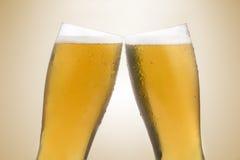 Beer glasses making a toast. Pair of beer glasses making a toast. Beer splash Royalty Free Stock Image