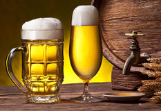 Beer glasses, old oak barrel and wheat ears. Royalty Free Stock Photos