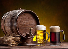 Beer glasses, old oak barrel and wheat ears. Beer glasses, old oak barrel and wheat ears on wooden table stock photography