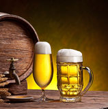 Beer glasses, old oak barrel and wheat ears. Royalty Free Stock Photography