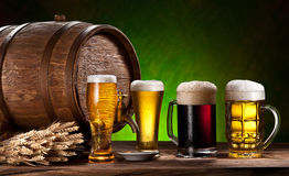 Beer glasses, old oak barrel and wheat. Royalty Free Stock Images