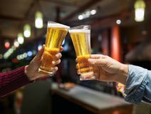 Beer glasses raised in a toast. Close-up hands with glasses. Blurred bar interior at the background Stock Photos