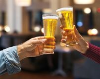 Beer glasses raised in a toast. Close-up hands with glasses. Blurred bar interior at the background Royalty Free Stock Photo