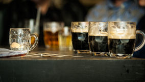 Beer glasses on the table of a bar. Horizontal colour image of half full beer glasses on the table of a bar, alcohol, under age drinking Stock Images