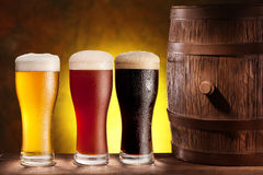 Beer glasses with a wooden barrel. Three beer glasses with a wooden barrel. Background - dark yellow gradient stock image