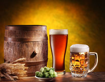 Beer glasses with a wooden barrel. Background - dark yellow gradient stock image