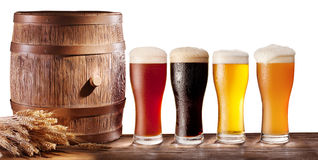 Beer glasses with a wooden barrel. Assortment of beer glasses with a wooden barrel on a white background royalty free stock photography