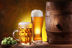 Beer glasses with a wooden barrel. Stock Photos