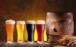 Beer glasses with a wooden barrel. Background - dark yellow gradient royalty free stock photography