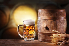 Beer glasses with a wooden barrel. Stock Images