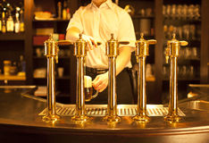 Beer. Gold beer in the hand and beer taps Royalty Free Stock Images