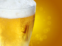 Beer with golden bokeh. Glass of beer on a gold background with golden bokeh Stock Photo
