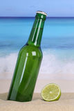 Beer in green bottle on the beach and sea Royalty Free Stock Photo