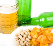 Beer green bottle and potato chips, pistachios Royalty Free Stock Photo