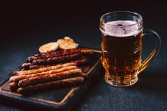 Beer and grilled sausages. oktoberfest, bar food. Beer and appetizing snacks. mug of craft lager and wooden board with homemade grilled sausages. oktoberfest stock photos
