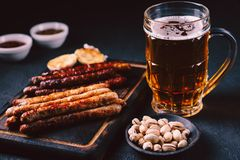 Beer and grilled sausages. oktoberfest, bar food. Beer and appetizing snacks. mug of craft lager and wooden board with homemade grilled sausages. oktoberfest royalty free stock photos