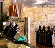 Beer growlers being filled up on a bar at a micro brew house tap room. The picture also shows rustic wood tap handles and a rock textured wall in the stock images