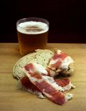 Beer and Ham. Delicatessen from spain. Pilsean beer and exquisite red ham whit some of rustic bread Royalty Free Stock Photos