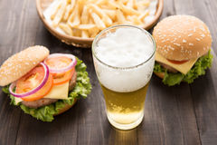 Beer with hamburger and french fries and on the wooden backgroun Royalty Free Stock Images