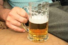 Beer in hand Stock Photo