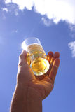 Beer in Hand. Beer glass and hand with blue sky Stock Images