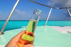 Beer on hand Caribbean in boat bow turquoise sea Stock Image