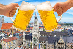 Beer mugs cheers with Munich Marienplatz in background. Beer mugs hands cheers with Munich Marienplatz in background - Oktoberfest concept stock photography