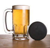 Beer and Hockey Puck. On wooden counter royalty free stock photo