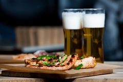 Beer and hot dog with grilled onions on wood background. Mixed grilled meat platter. Assorted delicious grilled meat Royalty Free Stock Photography