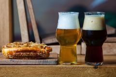 Beer and hot dog with grilled onions on wood background. Mixed grilled meat platter. Assorted delicious grilled meat Stock Photography