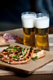 Beer and hot dog with grilled onions on wood background. Mixed grilled meat platter. Assorted delicious grilled meat Stock Image