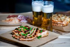 Beer and hot dog with grilled onions on wood background. Mixed grilled meat platter. Assorted delicious grilled meat Royalty Free Stock Photo