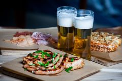 Beer and hot dog with grilled onions on wood background. Mixed grilled meat platter. Assorted delicious grilled meat Stock Photo