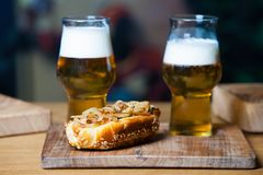Beer and hot dog with grilled onions on wood background. Mixed grilled meat platter. Assorted delicious grilled meat Royalty Free Stock Images