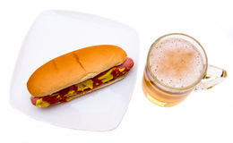 Beer and hot dogs from above. Beer and hot dogs on a white background seen from above royalty free stock images