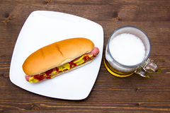 Beer and hot dogs on wood from above. Beer and hot dogs on wooden table seen from above royalty free stock photography