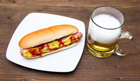 Beer and hot dogs on wood. En table stock photos