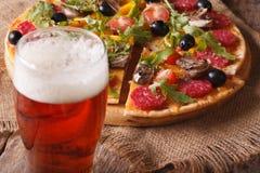 Beer and hot pizza with arugula close-up horizontal Royalty Free Stock Photo