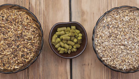 Beer ingredients, hops and malt. On wooden table top Royalty Free Stock Photography