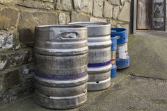 Beer kegs lined up against an outside wall Stock Photo