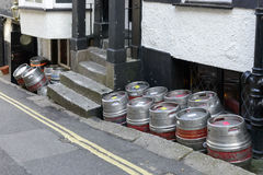 Beer kegs in street, Falmouth. Hoard of beer kegs piled up by a street in the village on southern coast of Cornwall stock images
