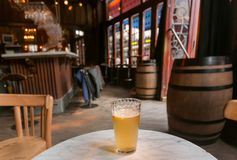 Beer with lemon for visitor of bar with vintage wooden furniture and stained-glass windows. Old bar in Brussels, Belgium Royalty Free Stock Photos