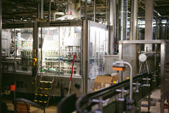 Beer manufacture line. Equipment for staged production bottling of Finished food products. Metal structures, pipes and tanks at en. Beer production line Royalty Free Stock Photo