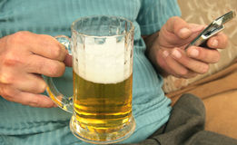 Beer and mobile in man hands Royalty Free Stock Images